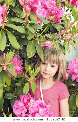 Young girl standing by a spring blooming bush.