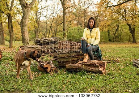 Beautiful young woman enjoying the autumn in the forest with her dog around.