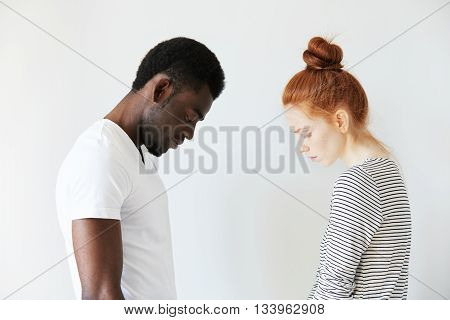 Sad Couple Looking Down With Their Heads Bowed In Front Of Each Other. Side View Portrait Of Two Sor