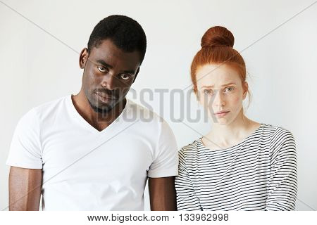 Portrait Of Young Caucasian Female With Red Hair, Angry And Disappointed With Her African Boyfriend,