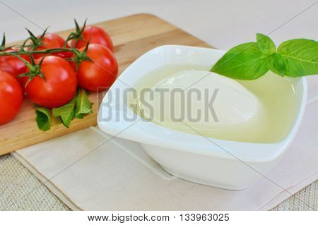 Mozzarella cheese in a porcelain dish with basil and tomatoes.