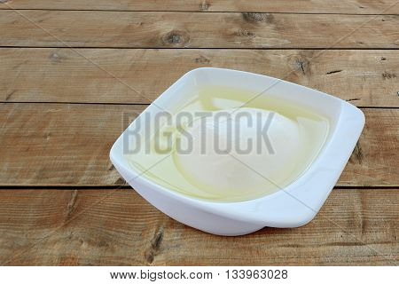 Mozzarella cheese soaking in brine in a porcelain dish over wooden table.