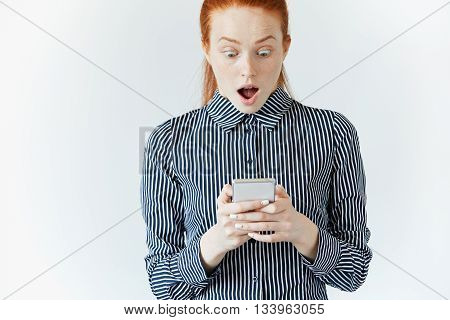 Shocking News! Business And Technology. Surprised Young Woman In Striped Shirt Using Smart Phone. Re