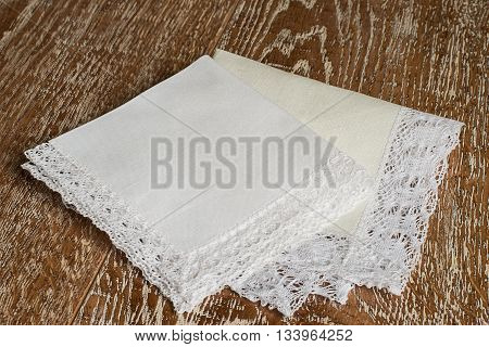 White handkerchiefs with a decorative trim on a brown wooden background.