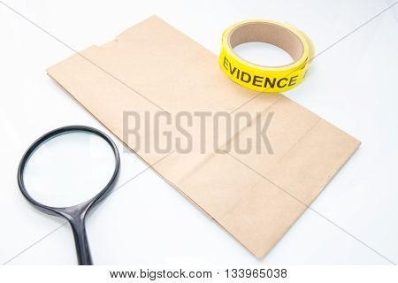 evidence bag with evidence tape and magnifying glass for crime scene investigation on white background