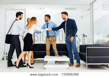 Group of young business people shake hands in the hall
