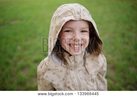 The ridiculous little girl looks in a camera and smiles. The girl on the head hood. She smiles genuine smile showing big white teeth.