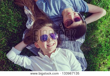 Little teenage boy and girl are lying on grass and boy wears earphones chillout top view