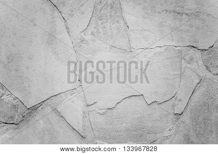 Rough stone wall with cracks of grey.