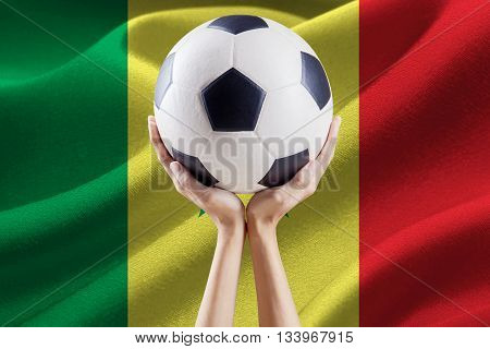 Soccer ball on the top of hands with national flag background of Senegal