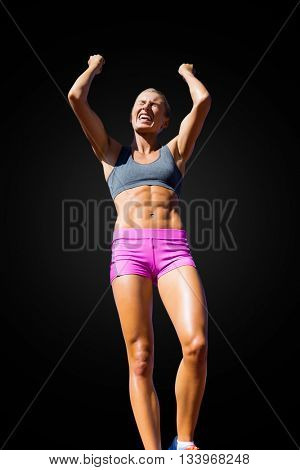 Low angle view of sportswoman celebrating her victory on a black background
