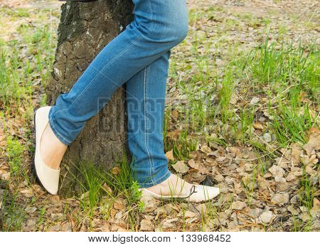 Young woman standing near a tree, legs, jeans shoes closeup.