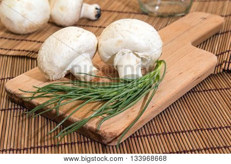 Mushrooms on a cutting board with salsola soda next