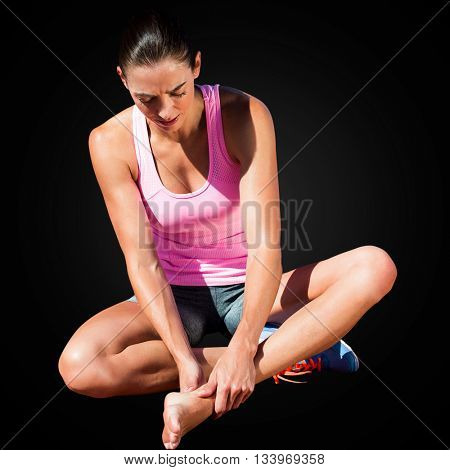 Sportswoman is hurting her foot in a black background
