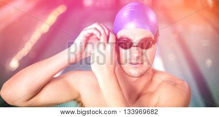 Fit man adjusting his goggles at the pool