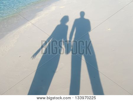 Shadows of man and woman, holding hands together on sand