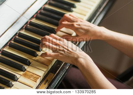 Old rusty piano, selective focus, woman's hands on keyboard