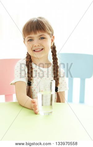 Cute little girl with glass of water at table