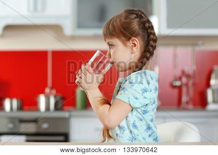Cute little girl drinking water in kitchen