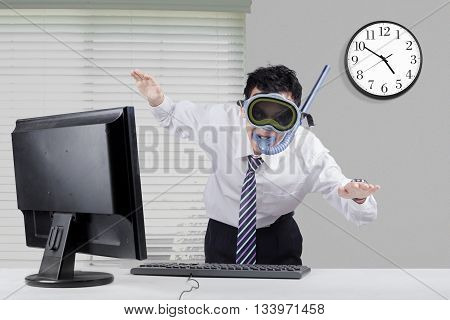 Young businessman wearing snorkeling equipment and posing to swim in the office with computer on desk