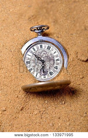 Vintage pocket watch on the beach buried in a sand