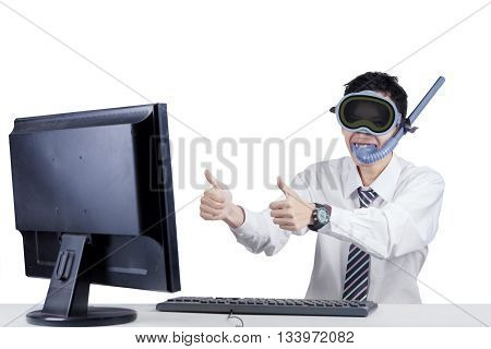 Young businessperson showing thumbs up on the monitor while wearing goggles and snorkel isolated on white background