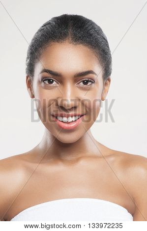 Beautiful young mulatto woman has a wonderful facial make-up. She is standing and relaxing. The lady is smiling and looking at camera with happiness. Isolated