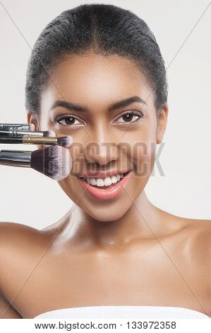 Portrait of cheerful mulatto girl holding various make-up brushes near her face. She is standing and smiling. The lady is looking at camera happily. Isolated