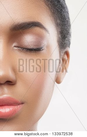 Close up of half of female face with beautiful make-up. Young african woman closed eyes with pleasure. Isolated
