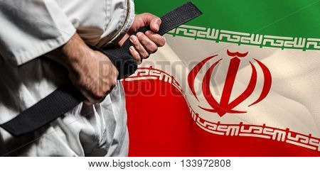 Fighter tightening karate belt against digitally generated iran national flag