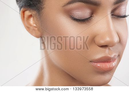 Close up of face of beautiful afirican girl with perfect make-up. She closed her eyes with relaxation. Isolated