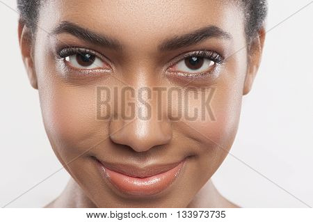 Close up portrait of female face with perfect skin. Attractive young mulatto woman is looking at camera with confidence and smiling. Isolated