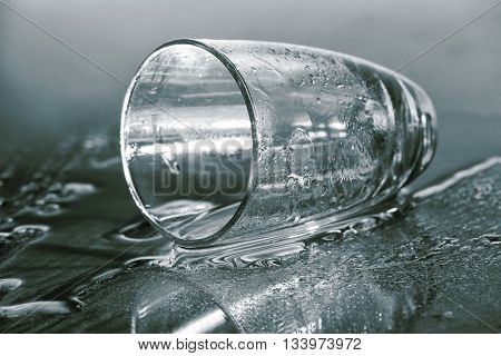 Overturned glass on gray background
