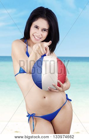 Portrait of beautiful young girl wearing bikini on the beach pointing at camera while holding a soccer ball with flag of France