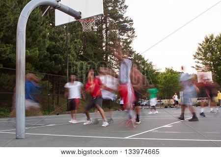 LAWRENCEVILLE, GA - MAY 2016:  Motion blur of young men playing a pickup game of basketball at a public park in Lawrenceville GA on May 27 2016.