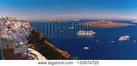 Panorama of Fira, modern capital of the Greek Aegean island, Santorini, with orthodox church, cruise ships, caldera and volcano, Greece