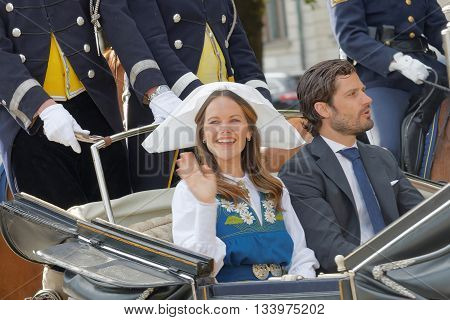 STOCKHOLM SWEDEN - JUN 06 2016: The swedish princess and prince Sofia and Carl Philip Bernadotte smiling and waiving to the audience from the royal coach on their way to celebrate the swedish national day.