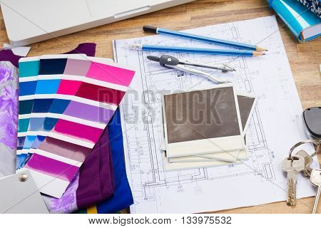 Interior designer's working table, an architectural plan of the house, color palette guide and fabric samples in lilac shades, copy space on instant empty photos
