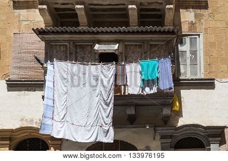 Typical traditional balcony in the capital of Malta - Valletta. Clean laundry getting dry in the sun.
