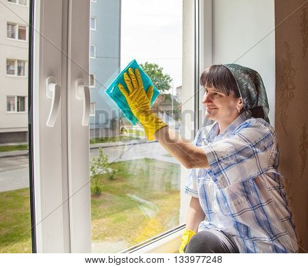 young smiling woman washes a window from the inside
