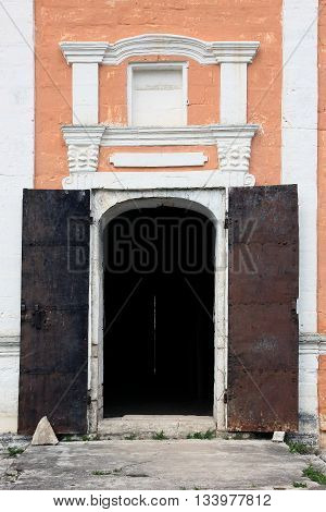 facade wall from limestone brick blocks with door frame with iron doors of old medieval russian orthodox church in old russian style near Staritsa Russia