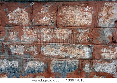 facade wall from white limestone brick blocks painted red color of old medieval church near Staritsa Russia