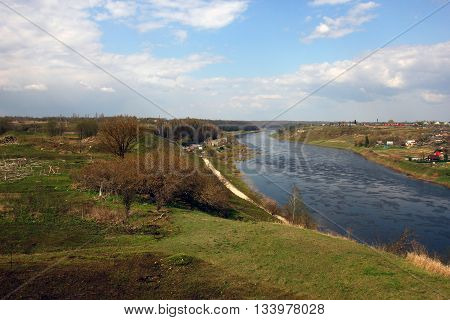 beautiful panoramic rural landscape with meadow hills river blue sky and village Staritsa Russia