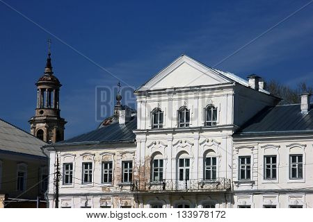 Vintage old public building in classical style and dilapidated orthodox church in the background