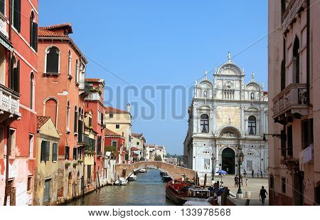 beautiful venetian landscape with view on venetian canal with bridge and cathedral