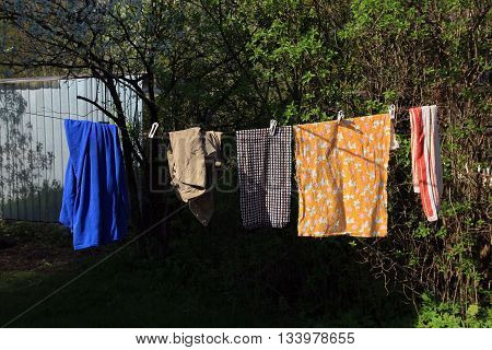 washed clean linen with clothespines drying on the rope outside in the village