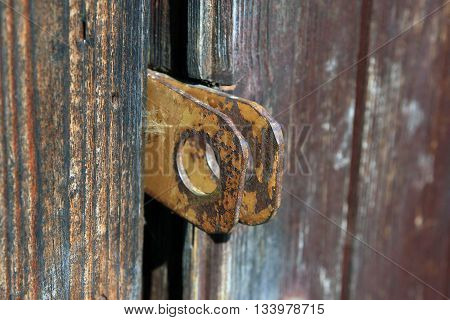 two old rusty metal steel eyelets for padlock on wooden door closeup