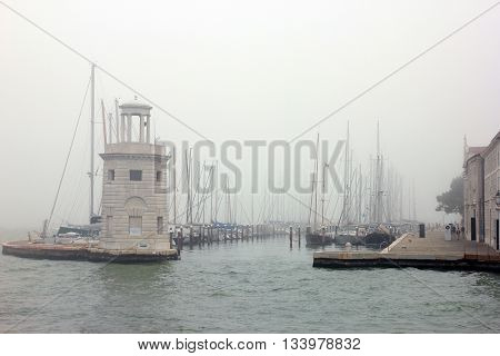 view from sea water on the old italian venetian boat dock with boats in Venice misty morning