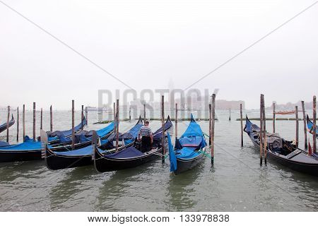 beautiful traditional venetian gondolas at the berth on the water at misty morning