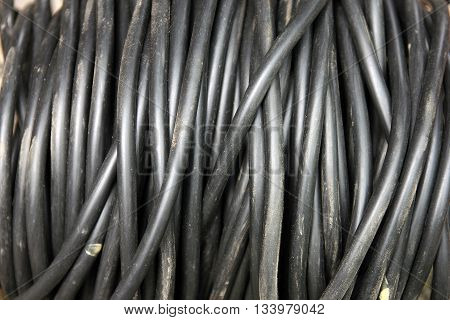 coil of big black dirty electrical insulated cable closeup foreground